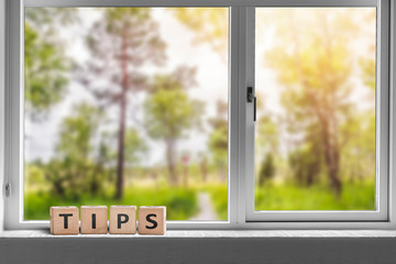 Tips sign in a window with a view to a green garden