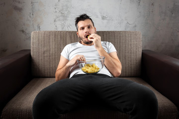 The guy in the shirt is lying on the couch, eating chips and watching a sports channel. The concept of laziness, frustration, procrastination, the person at home.