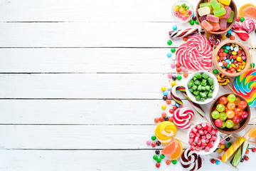 Colorful candies, jelly and marmalade on a white wooden background. Sweets. Top view. free copy space.