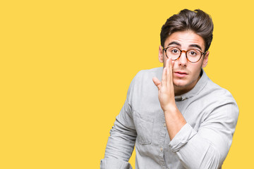 Young handsome man wearing glasses over isolated background hand on mouth telling secret rumor, whispering malicious talk conversation Wall mural