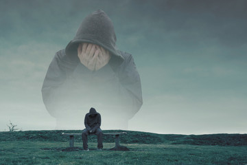 A double exposure of a hooded figure with his head in his hands over a lonely hooded figure sitting on a park bench, looking sad, lonely and depressed. With a cold, blue edit.