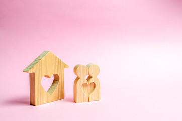 Pair of lovers stand near people at home with a heart. Happy family near the new home. The concept of finding a love nest. Affordable housing for young families and couples. Mortgage Valentine's Day.