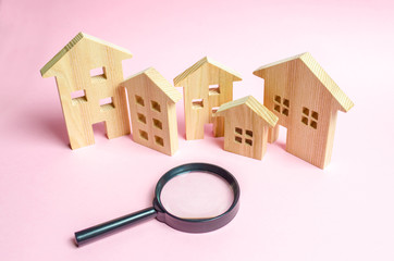 A lot of wooden houses on a pink background and a magnifying glass. The concept of finding a new home to buy or property to invest. Buying and selling real estate, investing. Romantic ancient city.
