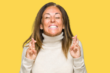 Beautiful middle age adult woman wearing winter sweater over isolated background smiling crossing fingers with hope and eyes closed. Luck and superstitious concept.