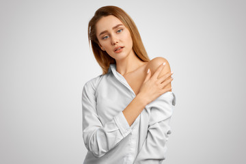 Sensual tender young woman in a white shirt bares one shoulder and shows off gorgeous skin. Skin care concept. Isolated on white wall