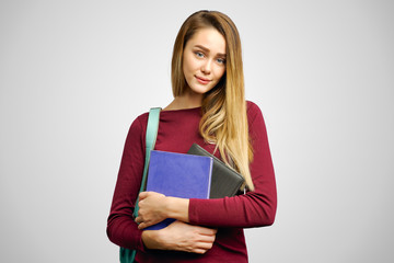 Cute young student holding notebooks and textbooks in her hands. The concept of teaching in a university college and education