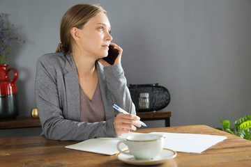 Serious businesswoman discussing project details on phone. Young woman in jacket speaking on cell and writing down notes. Business communication concept