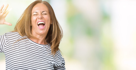 Beautiful middle age woman wearing stripes sweater over isolated background Dancing happy and cheerful, smiling moving casual and confident listening to music