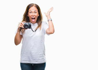 Middle age hispanic woman taking pictures using vintage photo camera over isolated background very happy and excited, winner expression celebrating victory screaming with big smile