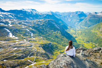 Happy tourist woman looking on Geirangerfjord and mountains landscape from Dalsnibba viewpoint, Norway