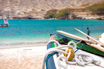 Old fishing boat on the shore. Boat with nets waiting for fishermen on the beach of Cape Verde.