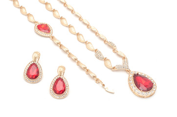 Wall Mural - set of golden earrings necklace and bracelet with a ruby isolated on white
