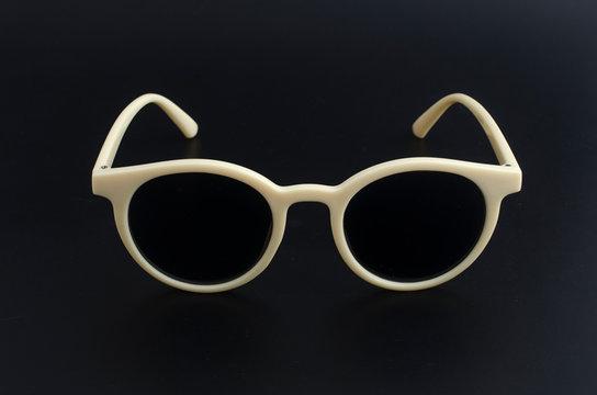 round retro sunglasses in plastic rim isolated on black