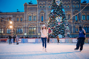 Young woman with skates on the ice rink