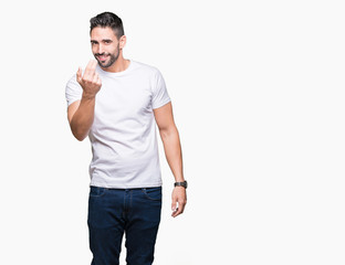 Handsome man wearing white t-shirt over white isolated background Beckoning come here gesture with hand inviting happy and smiling