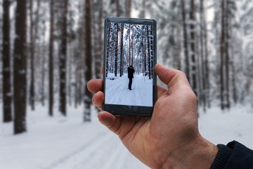 photo session in the winter forest, photographing on the smartphone of another photographer