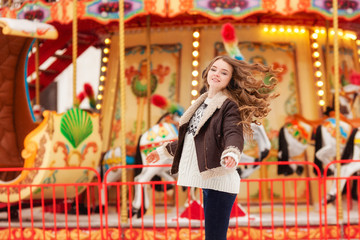 Beautiful happy woman with long vawy hair smiling over winter carousel .