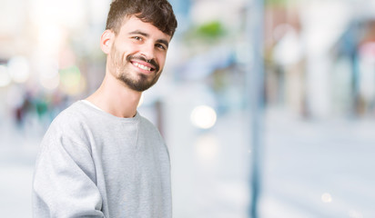 Young handsome man wearing sweatshirt over isolated background Inviting to enter smiling natural with open hand