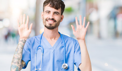 Young handsome nurse man wearing surgeon uniform over isolated background showing and pointing up with fingers number ten while smiling confident and happy.