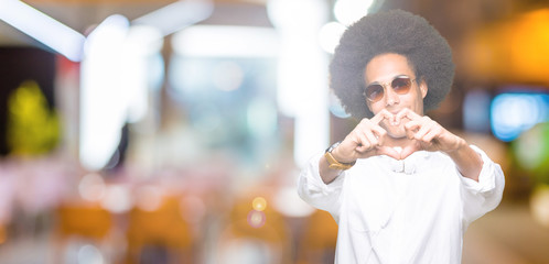 Young african american man with afro hair wearing sunglasses and headphones smiling in love showing heart symbol and shape with hands. Romantic concept.