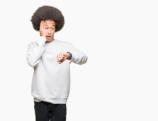 Young african american man with afro hair wearing sporty sweatshirt Looking at the watch time worried, afraid of getting late