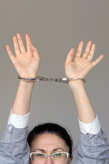 Close-up. Business woman in handcuffs isolated on gray background. Arrested or arrested terrorist in handcuffs. Criminal hands female locked in handcuffs. Hands in front.