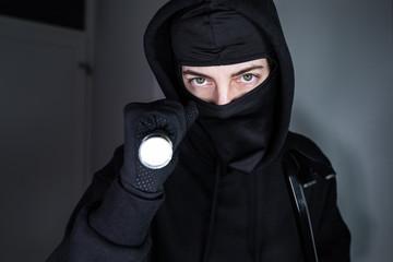 Einbrecher mit Brecheisen und Taschenlampe im Hausflur