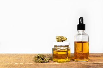 Medizin Cannabis Knospen und als Öl in Glas Flasche und Dose auf Holzuntergrund