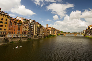 Morning Exercise - A lone oarsman rows along the Arno River on a beautiful summer morning. Ponte Vecchio over River Arno. Florence, Italy