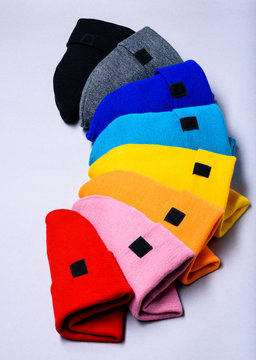 Knitted beanie hats. Colorful clothes items. Top view, copy