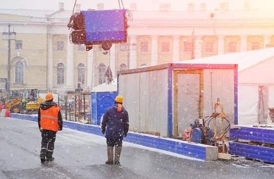 Unloading equipment for construction works in the city centre. Civil engineer at construction site is inspecting ongoing works in difficult winter conditions