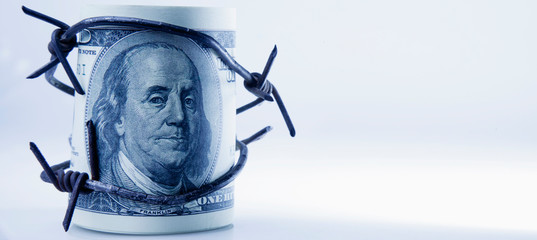 Economic warfare, sanctions and embargo busting concept. US Dollar money and barbed wire. Wall mural