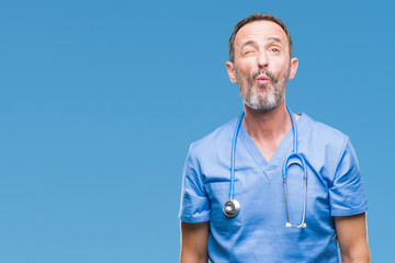 Middle age hoary senior doctor man wearing medical uniform over isolated background making fish face with lips, crazy and comical gesture. Funny expression.