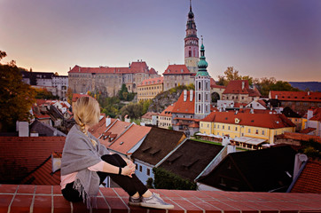 The blonde looks at the panorama of the city, tiled roofs and towers of the beautiful Czech Krumlov. Travel concept. Travel happy emotions. Lifestyle