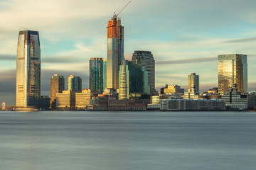 View on Jersey city skyscraper from Hudson river at sunrise with long exposure