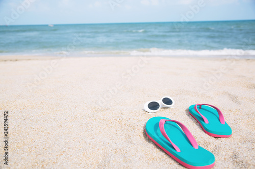 e1fea91c4329 slipper of foot in sandals shoes with sunglasses and Blue ocean wave water  distribution on sandy white beach