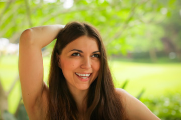 Close up portrait of carefree caucasian young woman posing with different emotions in green summer park.