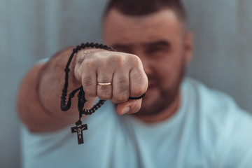 Close up portrait of man in a white t-shirt with Catholic prayer rosary beads in a hand
