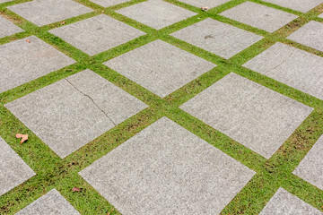 Pattern of square cement floor tiles with green grass field, perspective view.