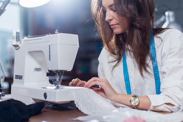 Cropped image of female tailor stitching fine lace with sewing machine sitting in dressmaking studio