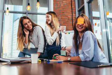 Two girls laughing at their friend with a sticky note on her face. Group of female students relaxing having fun in classroom during a break