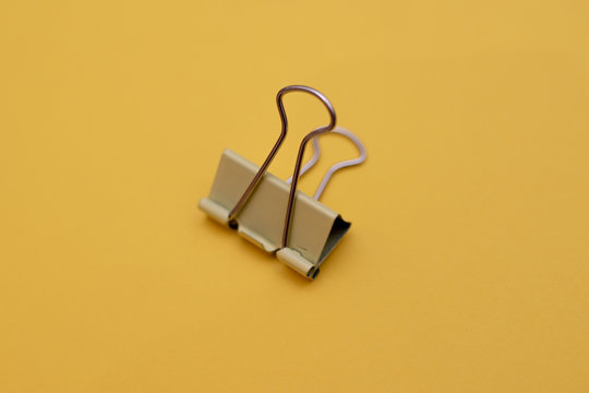 Yellow binder clip close up isolated on yellow background