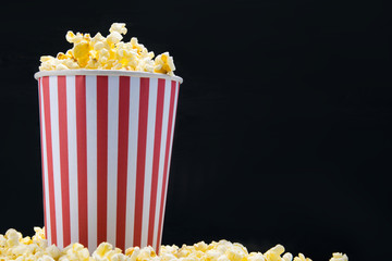 on a black background, a bucket of popcorn, with space for writing