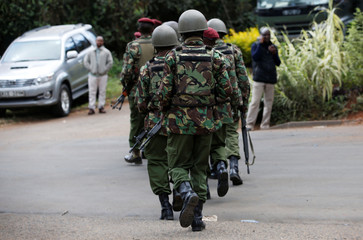 Kenyan policemen walk from the scene where explosions and gunshots were heard at the Dusit hotel compound in Nairobi