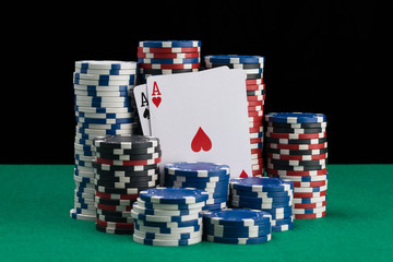 two cards are in a stack of poker chips on a green table
