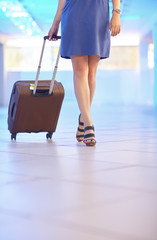 Young woman in blue dress walks around the airport hall and carrying a suitcase