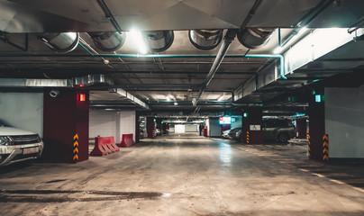 Illuminated underground car parking interior under modern mall with lots of vehicles