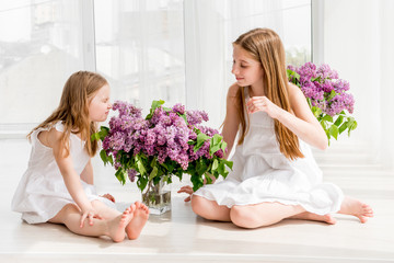 Smiling child girls with lilac bouquet