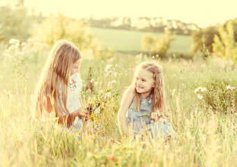 Two little sisters weave wreaths of flowers