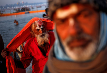 """Sadhus or Hindu holy men leave after taking a holy dip at Sangam, the confluence of the Ganges, Yamuna and Saraswati rivers, during """"Kumbh Mela"""", or the Pitcher Festival, in Prayagraj"""